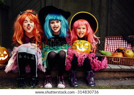 Funny girls showing tongues and looking at camera on Halloween night - stock photo
