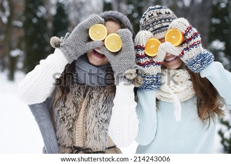 Funny girls with natural vitamins in winter  - stock photo