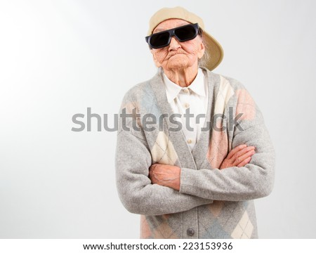 Funny grandma's studio portrait  wearing eyeglasses and baseball cap, who stands for her right,  isolated on white - stock photo