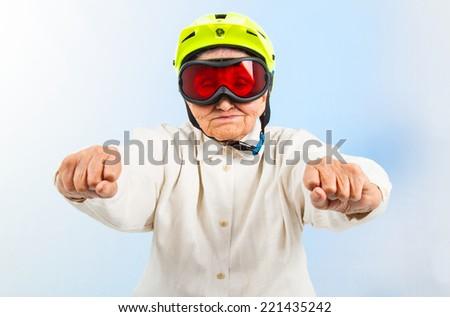 funny grandma wearing a yellow bicycle helmet and ski  goggles  - stock photo
