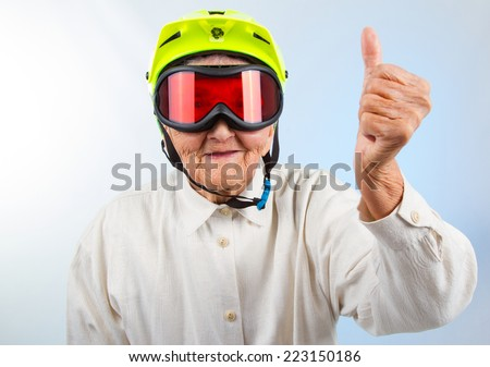 funny grandma wearing a yellow bicycle helmet and ski  goggles and showing thumbs up - stock photo