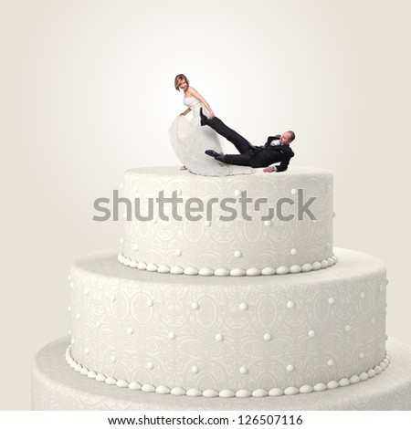 funny groom and bride on cake top - stock photo