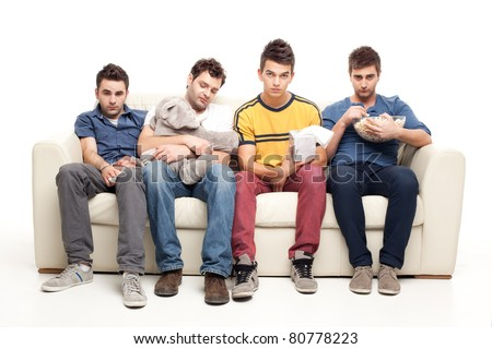 funny group of young men watching sad movie sitting on a couch - stock photo