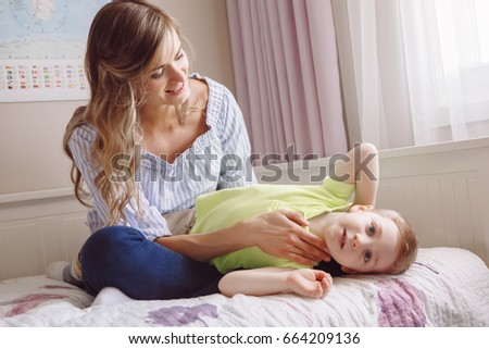 Funny group portrait of beautiful young white Caucasian mother and toddler child boy, playing together on bed in bedroom, having fun, natural candid family lifestyle