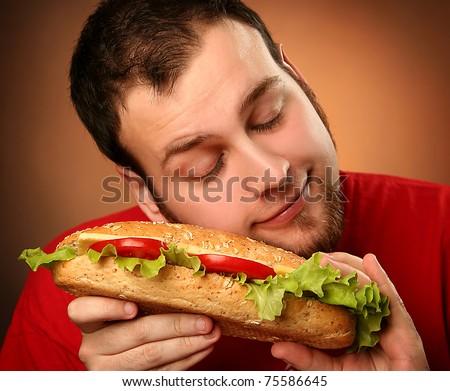 funny guy eating hamburger on red background - stock photo