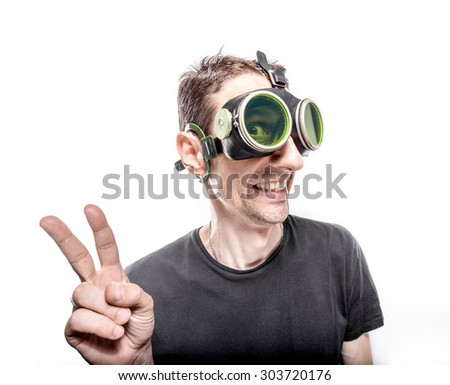 Funny guy in green vintage goggles. Hand with two fingers up in the peace or victory symbol. - stock photo