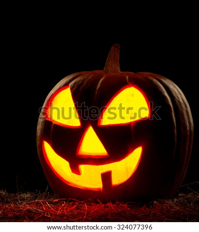 Funny Halloween pumpkin on black background. Scary glowing faces. - stock photo