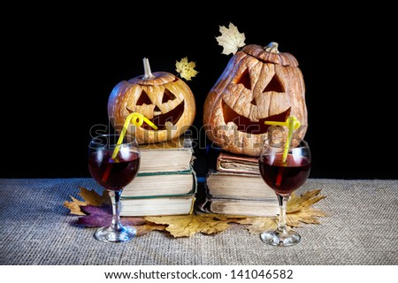 Funny Halloween pumpkins drinking wine on the heap of books at black background - stock photo