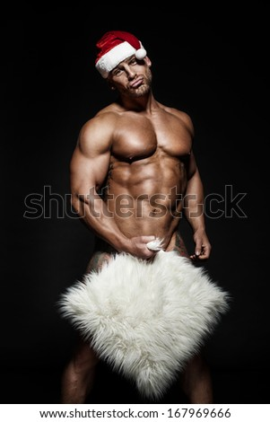 Funny handsome naked Santa Claus posing on black background looking at camera. - stock photo
