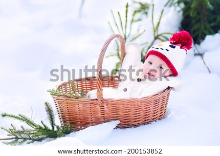 Funny happy baby boy wearing a warm snow suit and a red knitted snowman hat laying in a basket as a Christmas present in a beautiful winter park - stock photo