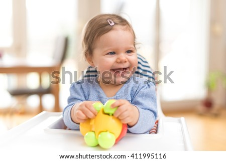 Funny Happy Baby Is Laughing And Playing With A Toy