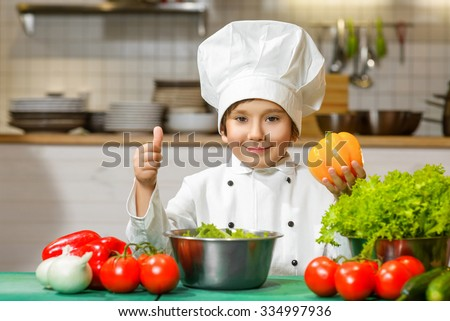 Funny happy chef boy holding bell pepper or cooking at restaurant kitchen. concept of vegetarianism