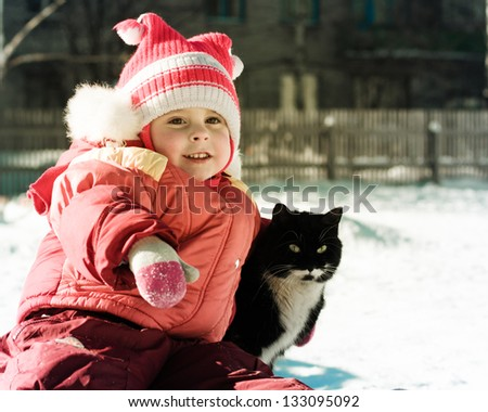 Funny happy child playing with cat outdoors in winter. - stock photo