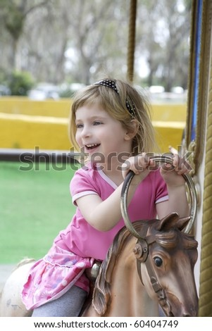 funny happy gesturing little blond girl playing on horses merry go round - stock photo
