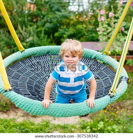 Funny happy kid boy having fun chain swing on outdoor playground. child swinging on warm sunny summer day. Active leisure with kids. - stock photo