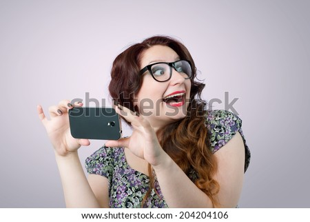 Funny happy lady with a smartphone on pink background - stock photo