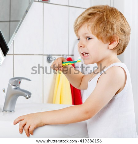 Funny happy little boy learning brushing his teeth in domestic bath. Kid learning how to stay healthy. Health care concept. - stock photo