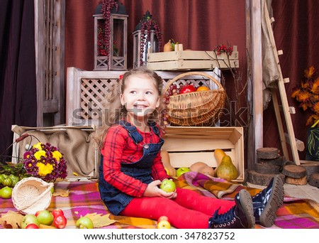 Funny happy little girl sitting on a wooden floor with a basket of green apples. A girl wearing a plaid red shirt, denim sundress, red tights and boots