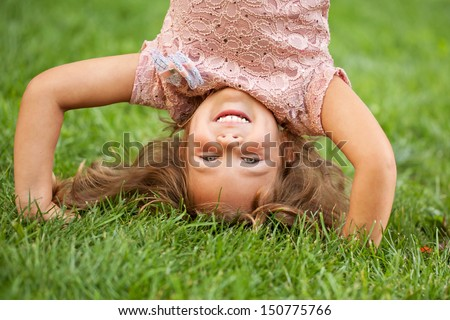 Funny happy little girl standing on her head on the grass in the park. Childhood concept, ready for your text, logo or symbols. - stock photo