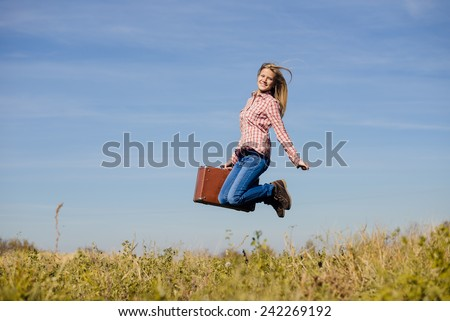 Funny happy teenage girl jumping with retro suitcase over blue sky copy space background - stock photo