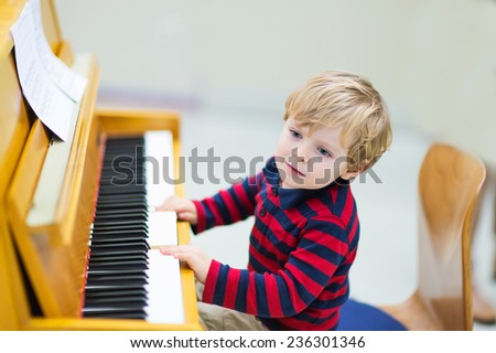 Funny happy toddler boy playing piano. Early music education for little kids. child at school, learning music instrument. - stock photo