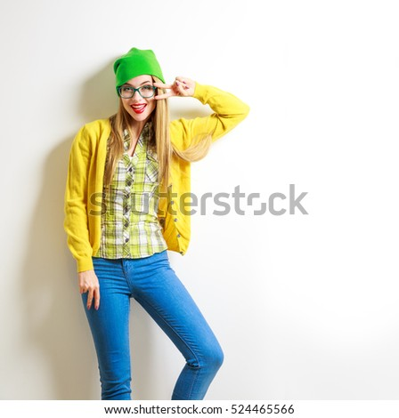 Funny Hipster Girl at White Wall Background. Street Syle Teenage Girl Smiling and Going Crazy. Trendy Casual Female Fashion Outfit in Spring or Autumn. Not Isolated Photo with Copy Space.