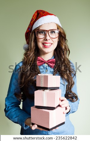 Funny hipster girl in super size eyeglasses wearing xmas santa hat holding three boxes of presents over olive copy space background - stock photo