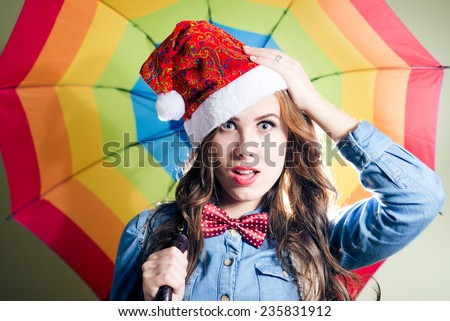 Funny hipster girl looking surprised wearing xmas santa hat over rainbow umbrella background - stock photo