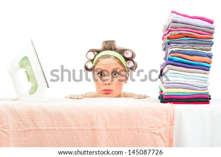Funny housewife has got a lot of laundry for ironing and she is wondering will this chores ever end,Too much laundry - stock photo
