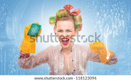 Funny housewife with scubberr cleaning window / glass . Foam / soap on glass - stock photo
