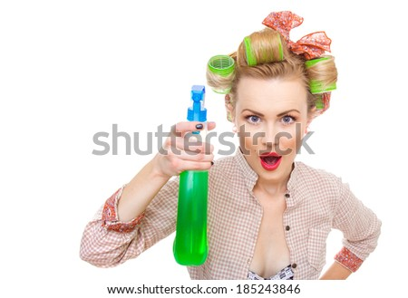 Funny housewife / woman spraying the cleaner on you, isolated on white. Glass or window cleaner - stock photo