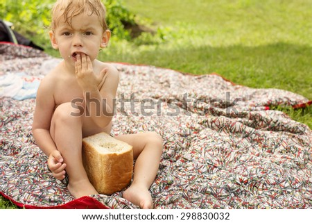 Funny Hungry Baby Eating Big piece of Bread Outdoor - stock photo
