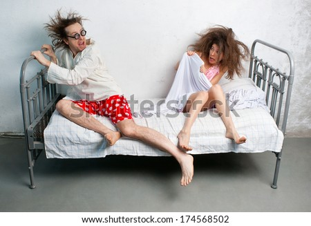 Funny husband and wife in the bed - stock photo