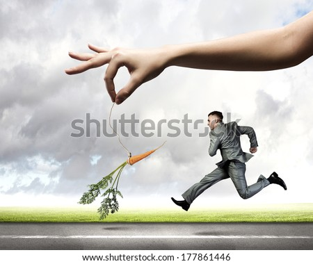 Funny image of businessman chased with carrot - stock photo