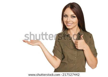 Funny image of surprised young woman showing open hand palm with copy space for product or text,  and gesturing thumb up, over white background - stock photo