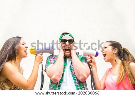 Funny image of two women screaming with megaphones in to  man's ears - shopping,funny,disagreement concept