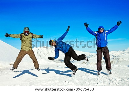 Funny jumping guys in winter mountains - stock photo
