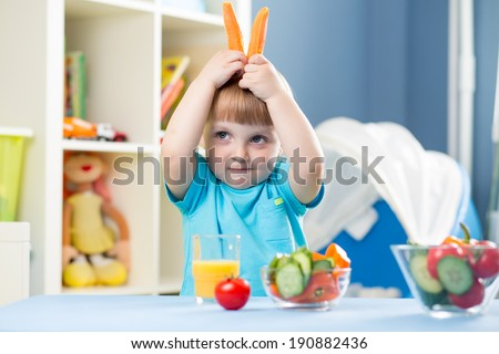 funny kid boy eating vegetables at home interior - stock photo