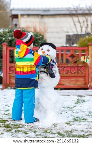 Funny kid boy in colorful clothes making a snowman, playing and having fun with snow, outdoors  on cold day. Active outdoors leisure with children in winter. - stock photo