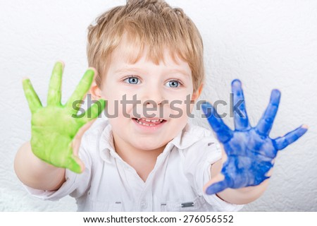 Funny kid child having fun with making handpaints with colors at home. Creative leisure for family and kids. - stock photo