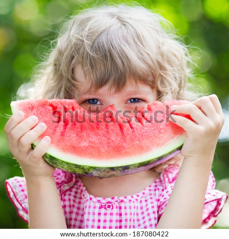 Funny kid eating watermelon outdoors in summer park. Child, baby, healthy food - stock photo