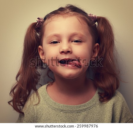 Funny kid girl showing tongue. Cool child joke. Vintage closeup portrait - stock photo