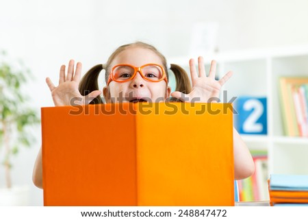 funny kid girl weared eyeglasses with book at home or kindergarten - stock photo