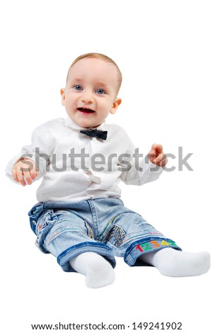 Funny kid in a shirt with a bow tie smiles sitting on the floor isolated on white background - stock photo