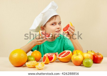 Funny kid in chefs hat with two slices of grapefruit at the table with fruits - stock photo