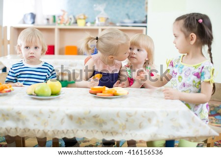 Funny kid kissing another one in day care centre - stock photo