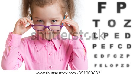 Funny kid putting on spectacles in ophthalmologist office - stock photo