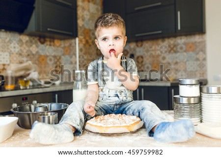 Funny kid sitting on the kitchen table in a roustic kitchen playing with flour and tasting a cake. He is covered in flour and looks funny. He puts his finger in the mouth. - stock photo