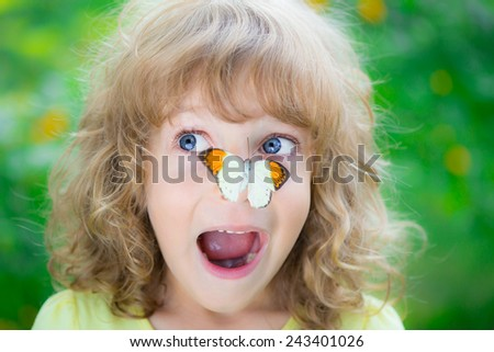 Funny kid with butterfly in spring park. Happy child playing outdoors. Unusual portrait - stock photo