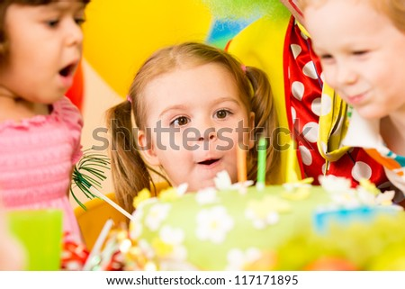 funny kids celebrating birthday party and blowing candles on cake